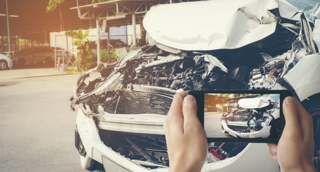 A man photographed his vehicle with accidental damage with a smart phone.Car Insurance Concept