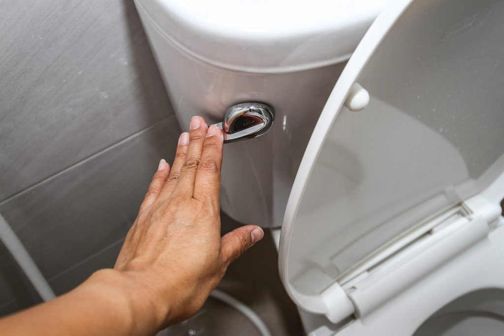 Hand flushing a toilet that will need toilet repair if they flushed the wrong thing